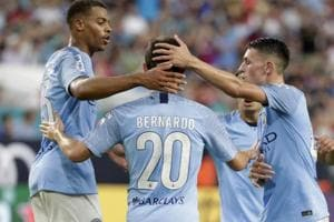 Manchester City midfielder Bernardo Silva is congratulated by teammates after scoring a goal against Bayern Munich.