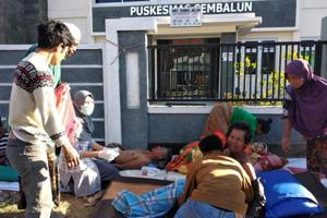 A paramedic gives treatment to injured people outside of a hospital after an earthquake hit Sembalun Selong village in Lombok Timur, Indonesia.