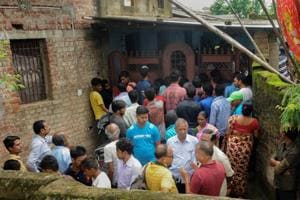 People gather outside the house where seven members of a family were found dead in Ranchi on July 30, 2018.