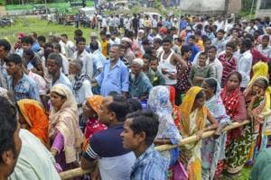 People wait to check their names on the draft of the state