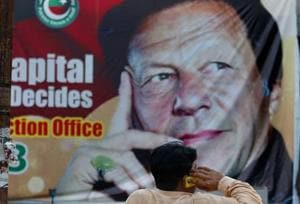 A Pakistani talks on his cell phone while he sits on a bench next to a big poster of Imran Khan, head of Pakistan Tehreek-e-Insaf party, at a market in Islamabad, Pakistan, Saturday, July 28, 2018. Khan is set to take oath as Pakistan's prime minister after his party emerged as the single largest party in the National Assembly in July 25 elections.