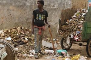 A sanitation worker is seen working without gloves, boots, or mask in Sector 52, Wazirabad village of Gurugram.