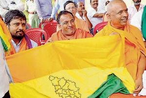 Protesters demanding separate statehood for 13 districts of north Karnataka unveil a regional flag in Belagavi on Tuesday.