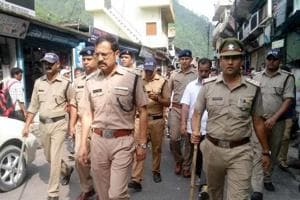 Police conduct a flag march after at Ghansali in Uttarkhand's Tehri Garhwal district. A mob of nearly 250 people thrashed 18-year-old Azad Alvi on Monday after he was caught with a minor Hindus girl inside a hotel in Ghansali town market, and paraded him with a garland of shoes around his neck. They also ransacked 13 shops of Muslim traders in the market.
