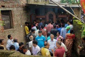 People gather outside the house where seven members of a family allegedly committed suicide, in Ranchi on Monday, July 30, 2018.