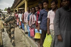 People stand in a queue to check if their names are included in the National Register of Citizens at a draft centre in Bur Gaon village, India, Monday, July 30, 2018.  India on Monday released a final draft of a list of its citizens in Assam.