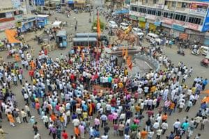 Maratha Kranti Morcha protesters block a road as police personnel keep a watch during a district bandh, in Solapur, Maharashtra on July 30.
