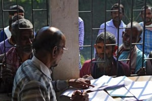 People wait to check their names on the first draft of the National Register of Citizens (NRC) at Goroimari in Kamrup district in Assam.