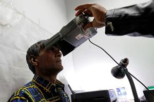 File photo of a man going through the process of eye scanning for the Unique Identification (UID) database system, also known as Aadhaar, at a registration centre in New Delhi. The Delhi government  on Tuesday said it will pay all pensions at old rates, which it had stopped last year due to lack of Aadhaar as proof.