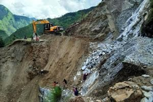 Workers clear a road after a landslide in Pithoragarh district.
