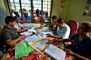 People wait to check their names on the draft list at the National Register of Citizens centre at a village in Nagaon district, Assam.
