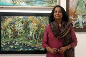 Artist Nisha Dial poses next to her artworks at her exhibition