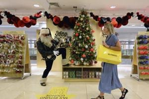A shopper walks past an actor dressed as Rock and Roll Santa, at the launch of the Christmas shop at Selfridges store in London.