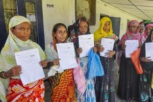 Women queue up to verify and check their names in the final draft of the National Register of Citizens (NRC), at Morigoan.