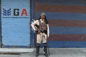 A paramilitary trooper stands guard in front of closed shops on the second day of strikes called by Kashmiri separatists against attempts to revoke articles 35A and 370 in downtown Srinagar on August 6, 2018.
