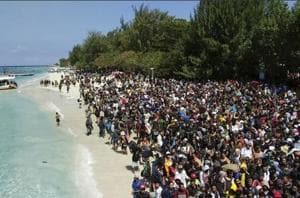 Tourists affected by a strong earthquake line up on a beach as they wait to be evacuated on Gili Trawangan Island, Indonesia, Monday.