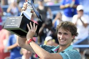 Alexander Zverev, of Germany, poses with the trophy after he defeated Alex de Minaur, of Australia, in the men