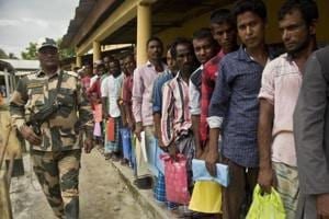 People stand in a queue to check if their names are included in the National Register of Citizens at a draft centre in Bur Gaon village in Assam on  July 30.