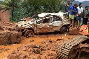 People inspect a damaged car following a landslide, triggered by heavy rains, in Idukki.