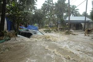 A car is submerged as roads and houses are engulfed in water following heavy rain and landslide in Kozhikode.