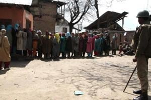 A security personnel stands guard as people line up to vote during the last panchayat polls held in Jammu and Kashmir in 2011.