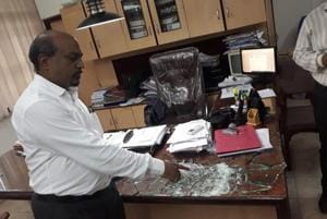 Anwar Shaikh, principal of Anjuman- E -Khairul Islam's Poona college of arts, commerce and science, shows the glass that the criminal broke while threatening him.