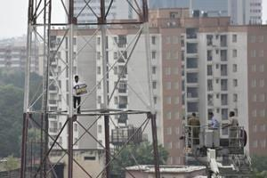 Fire fighters try to take down a man who climbed the Fire Station tower to demand special status for Andhra Pradesh at Connaught Place in New Delhi on Friday.