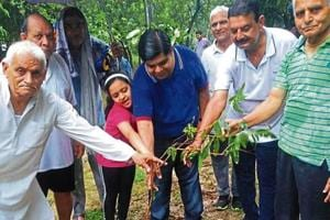 Residents of Sector 50  and Noida Authority staff at a plantation drive in B Block on Sunday.