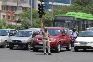 A traffic police home guard manages the traffic near Iffco Chowk on MG Road in Gurugram.