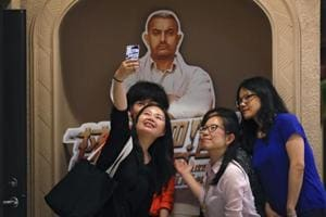 "Chinese women take a selfie with a poster of Indian Bollywood blockbuster film ""Dangal"" on display at a cinema in Beijing on May 22, 2017."
