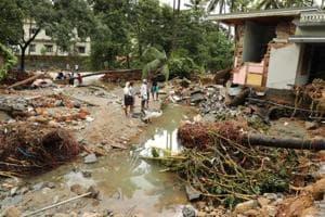 People walk by houses destroyed by flood waters at Kannappankundu in Kozhikode, in Kerala on August 10, 2018.