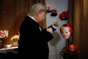 A performer in a Donald Trump mask hits a punching ball with German chancellor Angela Merkel's face at the Madame Tussauds wax museum in Berlin, Germany, on Tuesday.