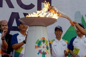 Officials light the 2018 Asian Games torch during the torch relay in Jakarta.