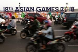 Commuters pass an Asian Games sign on the Ampera Bridge in Palembang, Indonesia.
