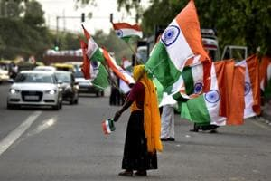 A woman sells the national flag on the eve of Independence Day .