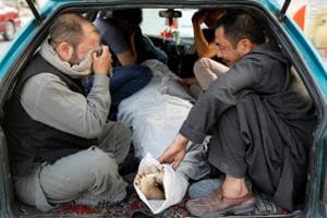 Afghan men mourn over a dead body after a blast outside a hospital in Kabul, Afghanistan August 15, 2018.