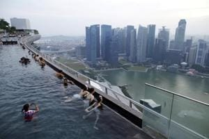 Tourists look out into the skyline of the city from an infinity pool atop the 57-storey Marina Bay Sands hotel in Singapore.
