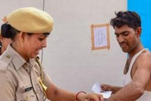 A police personnel removes a wristband of a candidate before entering the examination centre for the Rajasthan police constable recruitment exam 2018, in Bikaner on July 14, 2018.