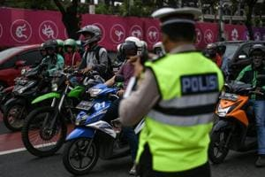 "An Indonesian policeman (R) stands next to a traffic light ahead of the 2018 Asian Games in Jakarta on August 17, 2018. - A police crackdown on petty crime in the run-up to the Asian Games in Indonesia has claimed dozens of lives, Amnesty International said on August 17, criticising what it said was an ""unnecessary and excessive"" campaign."
