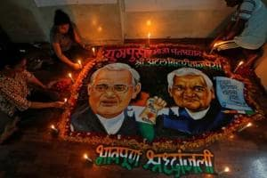 Students place candles around a painting featuring former Prime Minister Atal Bihari Vajpayee to pay him homage in Maharashtra.
