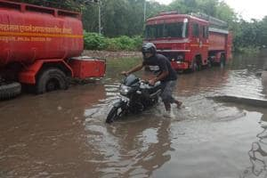 A biker hauling his vehicle after it developed a snag while riding on an inundated road in the area