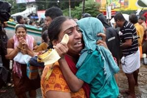 A woman cries as she holds her son after they were evacuated from a flooded area in Aluva in Kerala, on August 18, 2018.