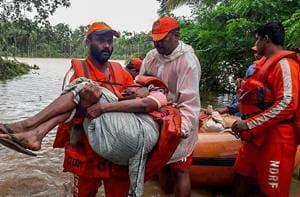 NDRF personnel rescue flood-hit people in Wayanad, Kerala on August 11.