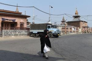 A Kashmiri woman walks in front of the Jamia Masjid grand mosque on the second day of strikes called by Kashmiri separatists in downtown Srinagar on August 6, 2018.