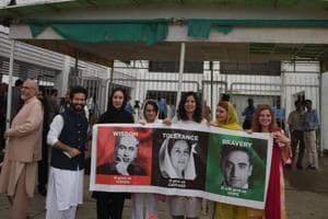 Supporters of Pakistan Peoples party hold a placard with the pictures of (L-R) late former Pakistani premier Zulfikar Ali Bhutto and his daughter late former premier Benazir Bhutto and grandson Bilawal Bhutto during the first session of the parliament after the general election, in Islamabad on August 13, 2018.