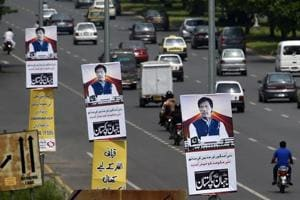 The posters of Pakistan prime minister Imran Khan are displayed along a highway in Islamabad on Saturday. Pakistan
