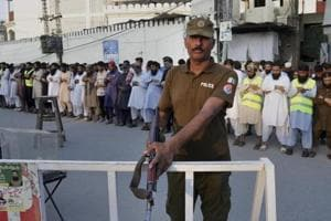 A Pakistani police officer stands guard while people offer funeral prayers in Lahore for the victims of a Friday suicide bombing in Mastung district of Baluchistan province, Pakistan that killed 149 people  in July 2018.