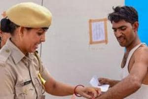 A police personnel removes a wristband of a candidate before entering the examination centre for the Rajasthan police constable recruitment exam 2018 in Bikaner on July 14, 2018.