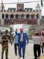 Punjab minister and former cricketer Navjot Singh Sidhu waves as he crosses the border to attend the swearing-in ceremony of Pakistan Prime Minister-elect Imran Khan, at Attari-Wagah border in Attari.