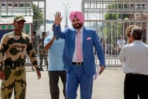 Punjab minister and former cricketer Navjot Singh Sidhu waves as he crosses the border to attend the swearing-in ceremony of Imran Khan, at Attari-Wagah border in Attari.
